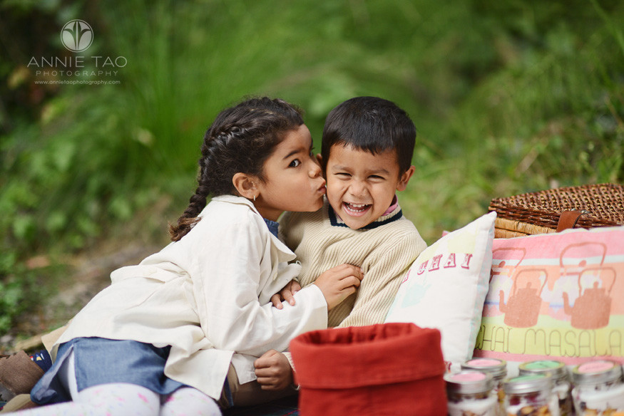 San-Francisco-lifestyle-children-photography-big-sister-leaning-in-to-kiss-young-brother-at-picnic