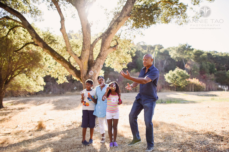 Bay-Area-lifestyle-family-photography-man-popping-bubbles-blown-by-his-children-during-hike