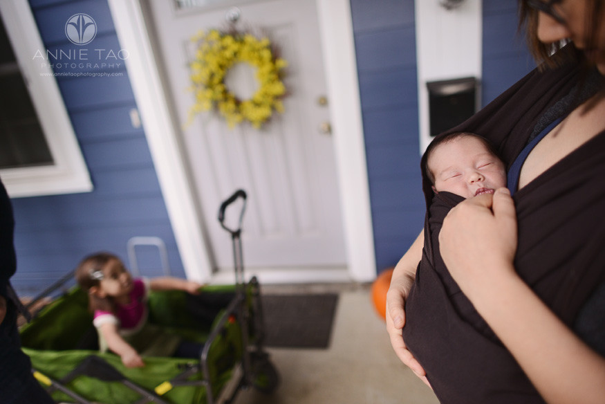East-Bay-lifestyle-newborn-photography-baby-sleeping-in-mommy-carrier-while-toddler-and-dad-watches
