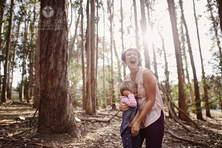 San-Francisco-lifestyle-family-photography-woman-putting-child-down-and-cracking-up-with-sunflare