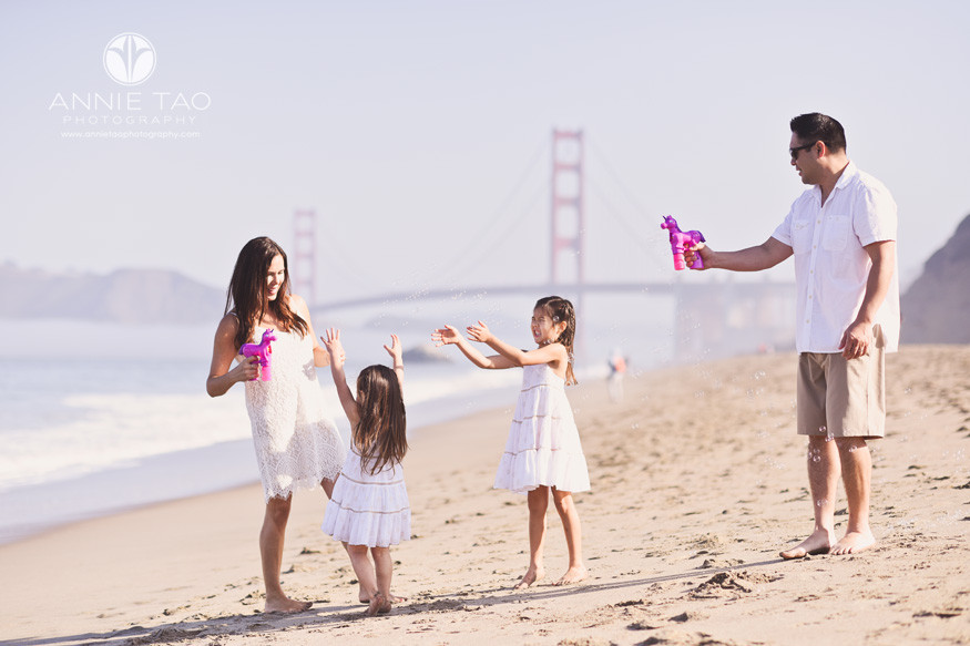 San-Francisco-lifestyle-family-photography-parents-with-pink-unicorn-bubbles-at-beach-with-daughters