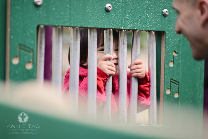 San-Francisco-lifestyle-children-photography-toddler-girl-smiling-at-dad-through-playground-bars