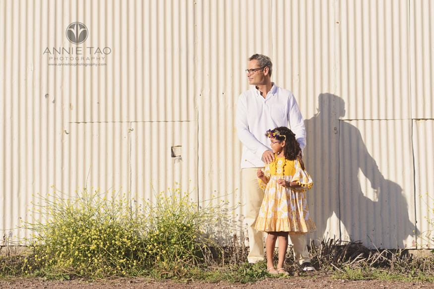 san-francisco-lifestyle-family-photography-father-holding-daughters-shoulders-by-yellow-wall-and-flowers
