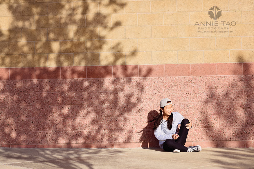 East-Bay-lifestyle-teen-photography-girl-sitting-against-wall-with-tree-shadows