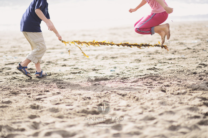 San-Francisco-lifestyle-family-beach-photography-sisters-jumping-with-seaweed