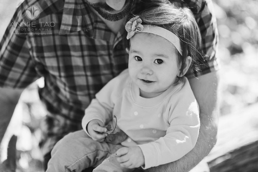 East-Bay-lifestyle-baby-photography-baby-holding-a-leaf-while-in-dads-arms-BxW