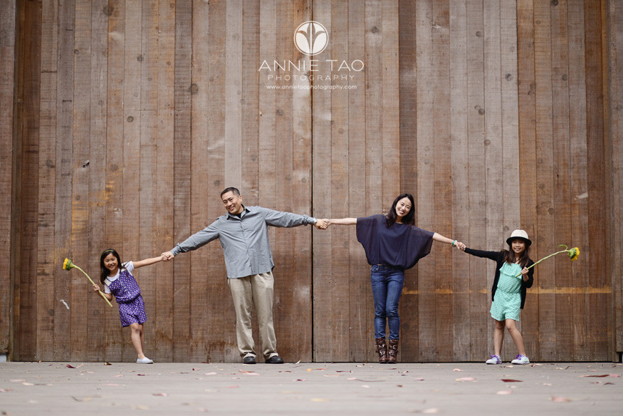 San-Francisco-lifestyle-family-photography-family-of-four-holding-hands-in-an-arc-by-wood-wall