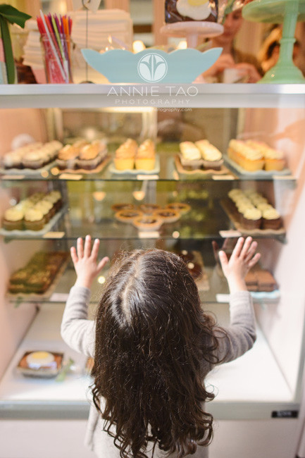 san-francisco-lifestyle-children-photography-preschooler-girl-looking-up-at-glass-cabinet-of-pastries