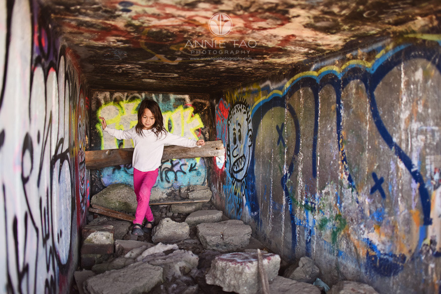 East-Bay-lifestyle-children-photography-young-girl-balancing-herself-in-graffiti-tunnel