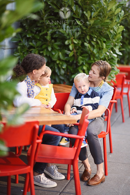San-Francisco-lifestyle-family-photography-parents-sitting-on-red-chairs-with-toddler-twins-on-laps