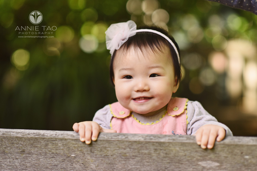 Bay-Area-lifestyle-baby-photography-smiling-baby-girl-holding-wooden-bench