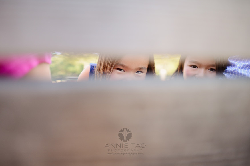 East-Bay-children-lifestyle-photography-two-sisters-peeking-through-bench-parents-are-on