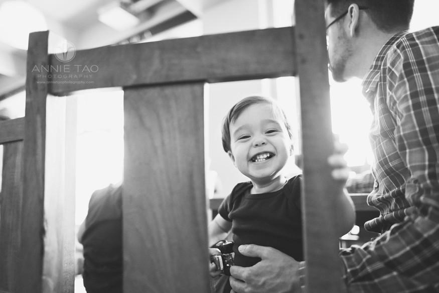San-Francisco-lifestyle-children-photography-toddler-boy-smiling-through-chair-slats-BxW