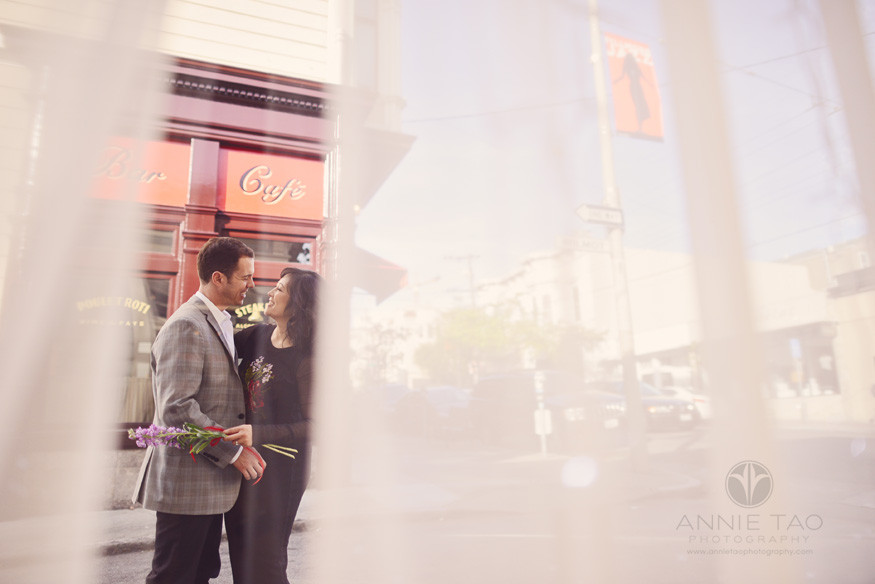 San-Francisco-lifestyle-engagement-photography-peeking-at-couple-having-a-moment-outside-store