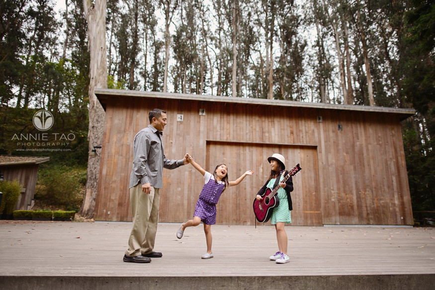 San-Francisco-lifestyle-family-photography-father-and-daughter-dancing-while-older-daughter-plays-guitar