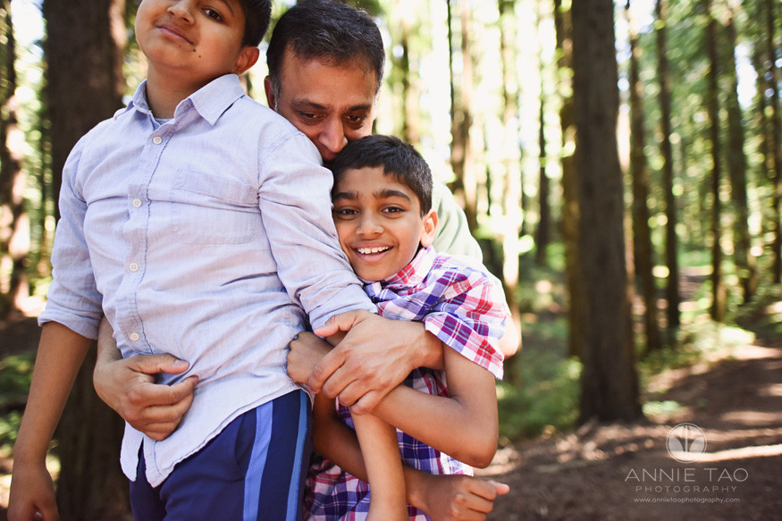 East-Bay-lifestyle-family-photography-father-surprised-older-children-with-hug-in-Forest