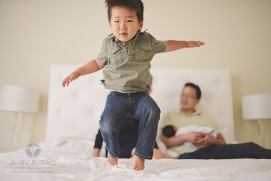 San-Francisco-lifestyle-family-photography-toddler-boy-jumping-on-the-bed-while-family-is-sitting