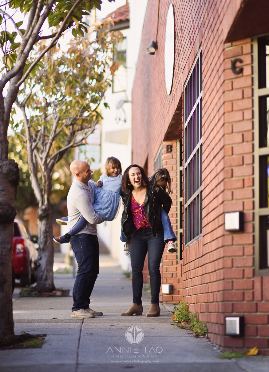 San-Francisco-lifestyle-family-photography-parents-giving-daughters-piggybacks-while-sisters-tickling-on-sidewalk