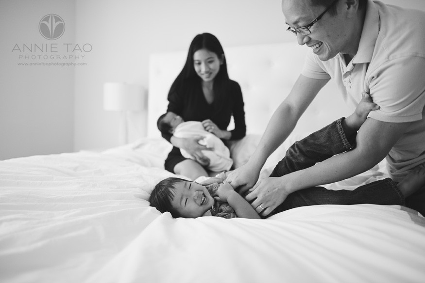 San-Francisco-lifestyle-newborn-family-photography-father-tickling-toddler-son-while-mother-holds-baby-in-bed-BxW