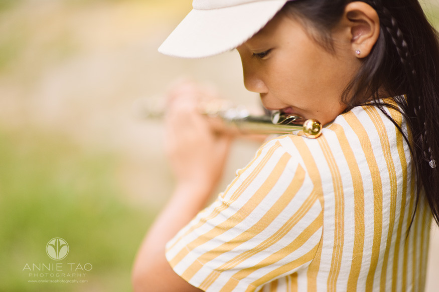 East-Bay-styled-children-photography-girl-blowing-in-gold-flute-closeup