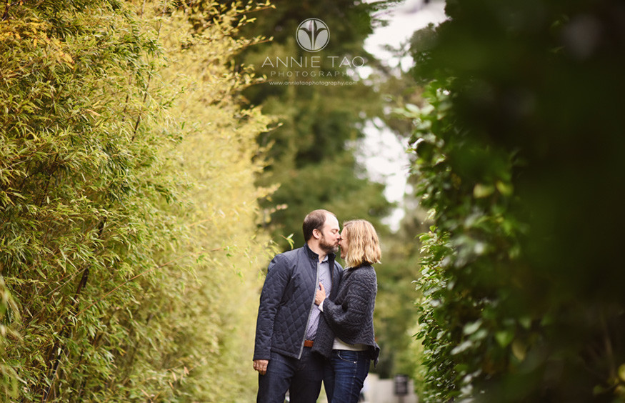 San-Francisco-lifestyle-couple-photography-man-leans-into-wife-for-kiss-among-bushes