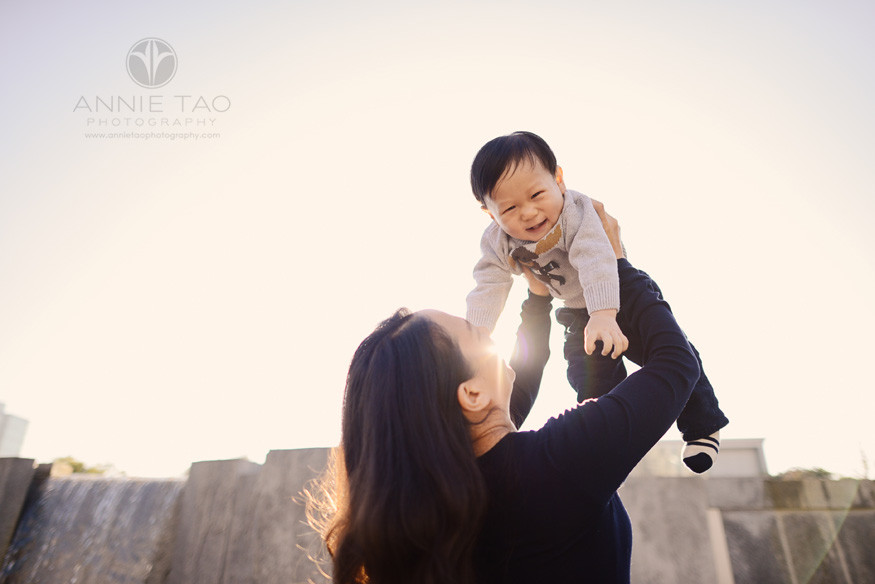 San-Francisco-lifestyle-baby-photography-12-month-old-baby-boy-laughing-while-mom-lifts-him-above-waterfall