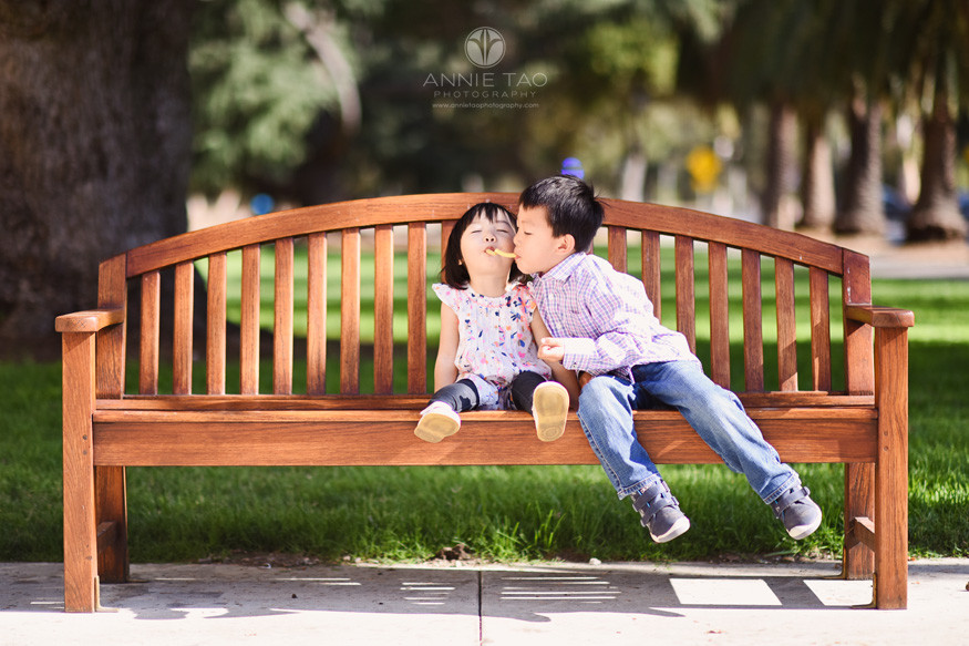 Bay-Area-lifestyle-children-photography-young-boy-and-toddler-sister-sitting-on-bench-touching-snacks-in-mouths