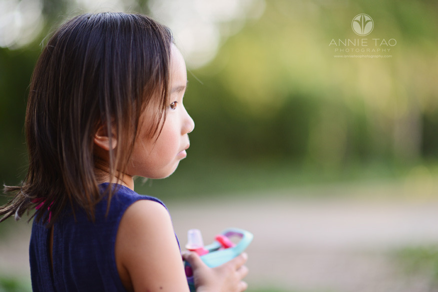 East-Bay-children-lifestyle-photography-young-girl-looking-beyond-while-holding-sippy-cup