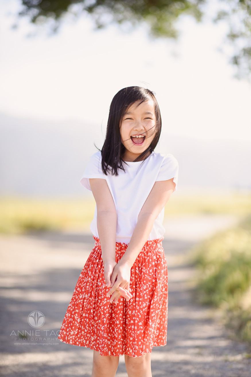 east-bay-lifestyle-children-photography-young-girl-with-coral-skirt-laughing-on-windy-day-LG