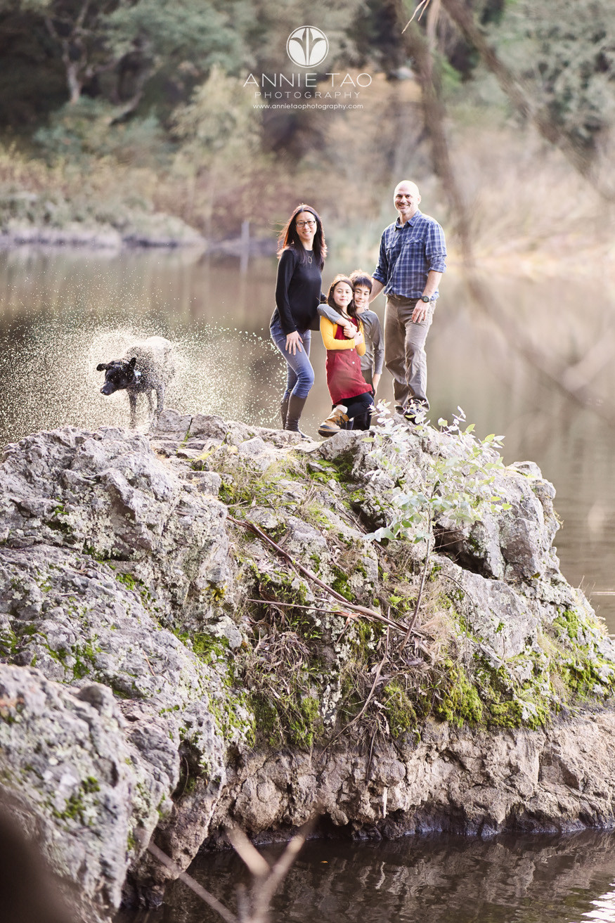 east-bay-berkeley-lifestyle-family-photography-standing-together-on-cliff-while-black-dog-shakes-off-water-by-lake