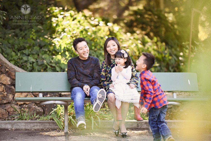 East-Bay-lifestyle-family-photography-parents-and-toddler-girl-sitting-on-bench-and-laughing-at-funny-son