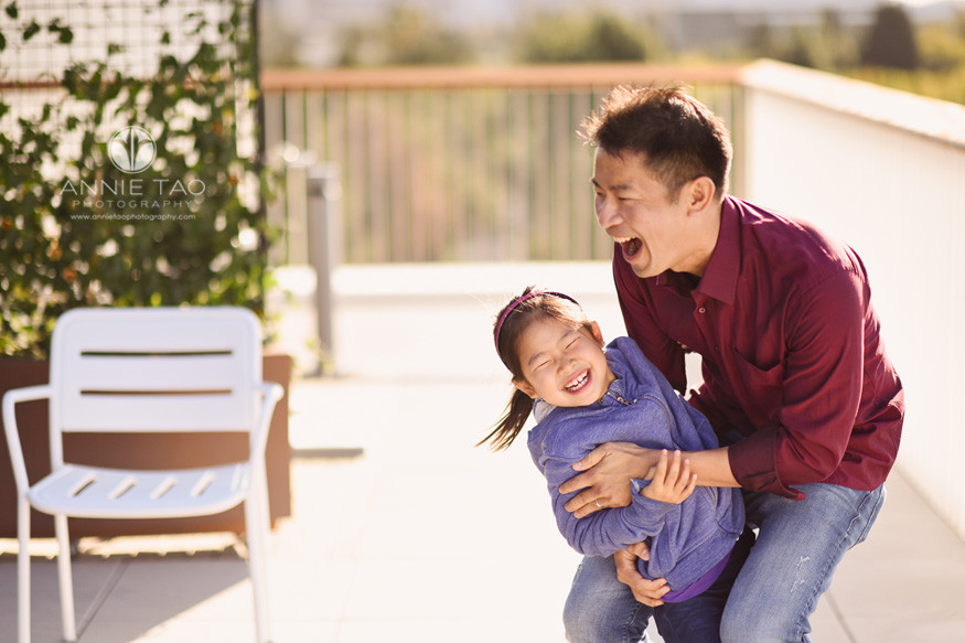 San-Francisco-Bay-Area-lifestyle-family-photography-father-laughing-while-putting-child-down-in-garden