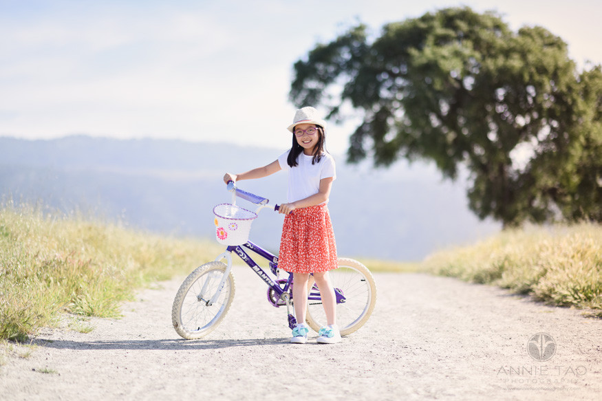 east-bay-lifestyle-children-photography-young-girl-with-hat-holding-bike-on-hillside