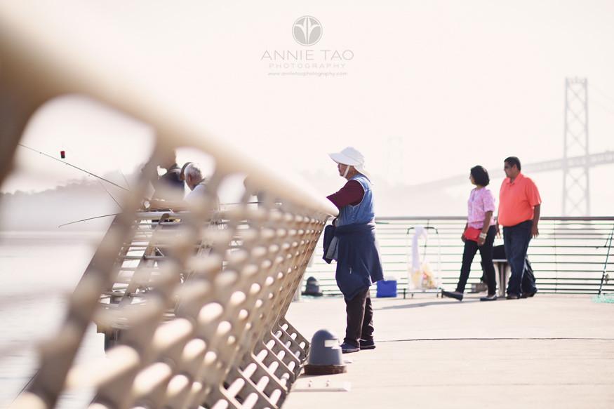 San-Francisco-lifestyle-couple-photography-couple-walking-behind-fishermen-at-pier