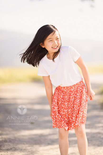 east-bay-lifestyle-children-photography-young-girl-with-coral-skirt-leaning-and-laughing-on-windy-day