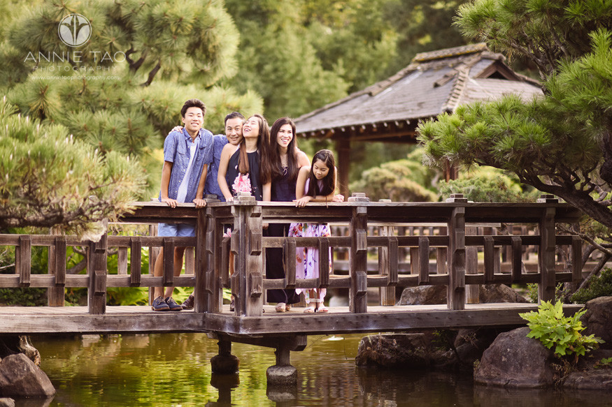East-Bay-lifestyle-family-photography-leaning-into-each-other-while-on-footbridge-in-japanese-garden