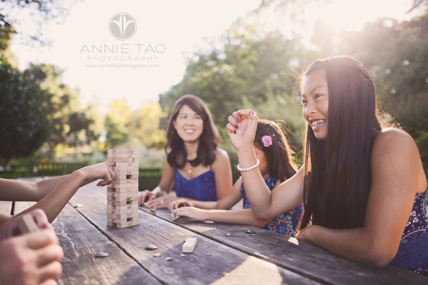 Bay-Area-San-Francisco-lifestyle-family-photography-family-playing-game-at-garden-picnic-table-with-sunflare