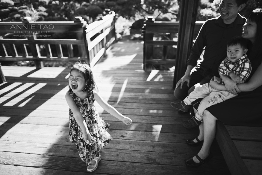 east-bay-lifestyle-children-photography-young-girl-twirling-while-family-smiles-in-teahouse-bxw