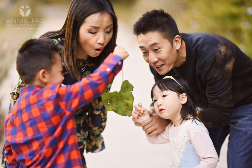 East-Bay-lifestyle-family-photography-mother-blows-bug-off-leaf-while-family-looks-on-and-toddler-girl-is-horrified