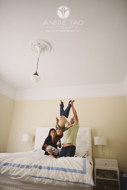 San-Francisco-lifestyle-newborn-family-photography-father-lifting-toddler-son-upside-down-while-mother-holds-baby-and-looks-worried