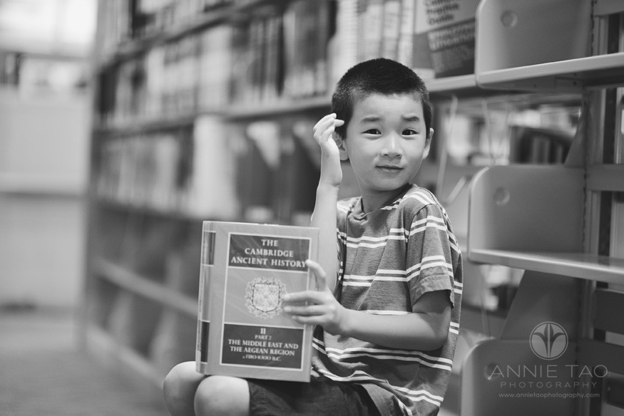 East-Bay-lifestyle-children-photography-library-young-boy-scratching-his-head-with-a-history-book-BxW