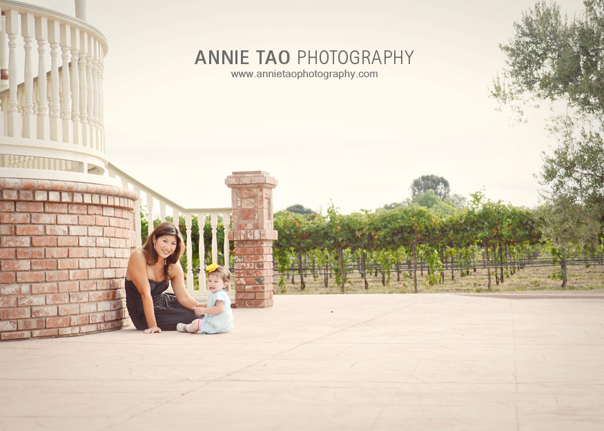 San-Francisco-East-Bay-family-photography-smiling-mom-and-baby-girl-sitting-by-Victorian-house