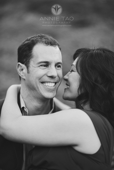 San-Francisco-lifestyle-engagement-photography-woman-whispering-to-her-fiance-while-sitting-on-his-lap-BxW