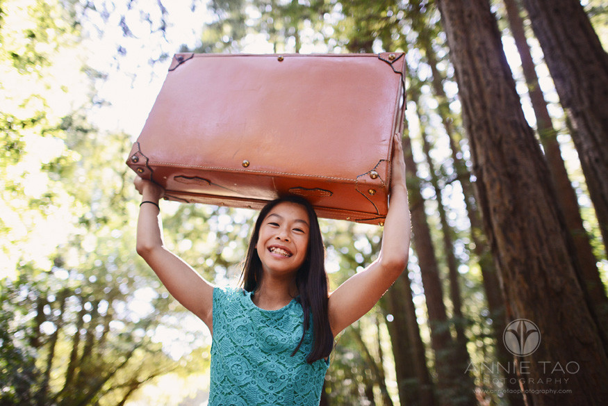 East-Bay-styled-children-photography-girl-carrying-suitcase-on-head-in-woods
