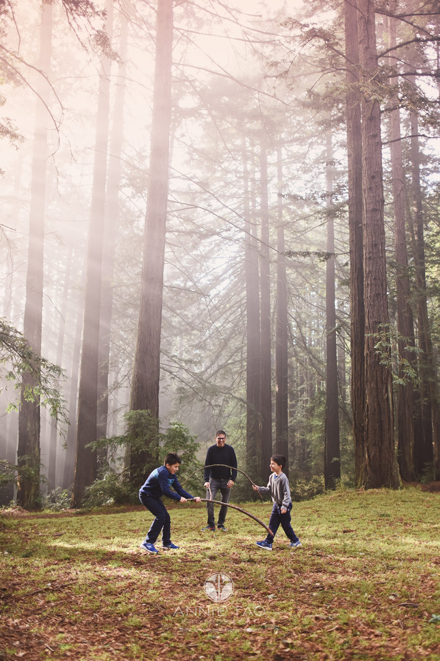 East-Bay-lifestyle-family-photography-two-boys-and-their-dad-playing-with-sticks-in-forest