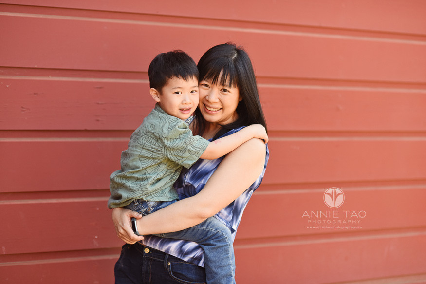 Bay-Area-lifestyle-family-photography-woman-holding-preschool-son-by-red-barn
