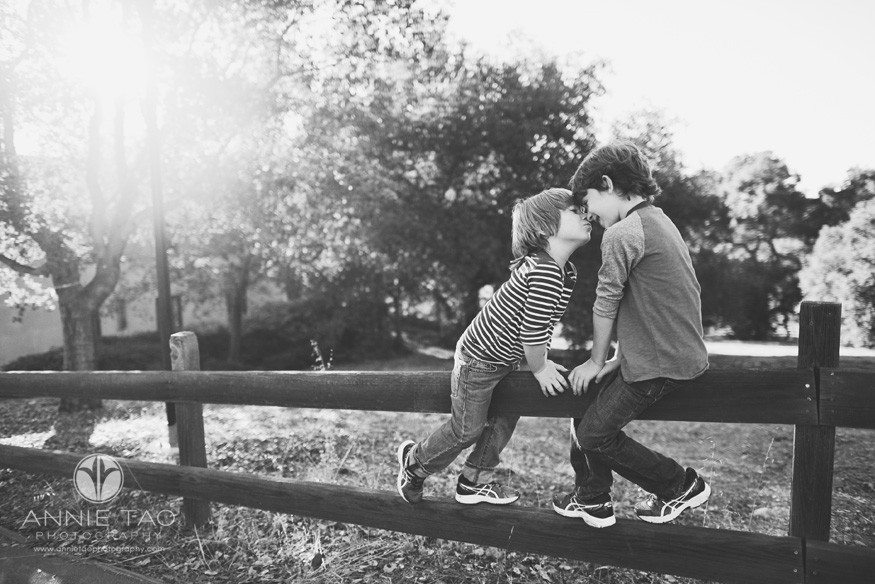 Bay-Area-lifestyle-children-photography-little-brother-kissing-big-brother-on-fence-BxW