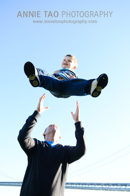 San-Francisco-Bay-Area-family-photography-dad-throwing-son-in-air-with-Bay-Bridge-behind