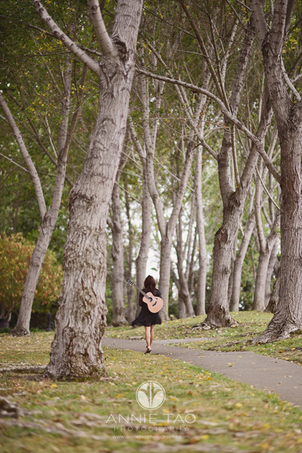 East-Bay-styled-photography-woman-with-guitar-walking-through-woods