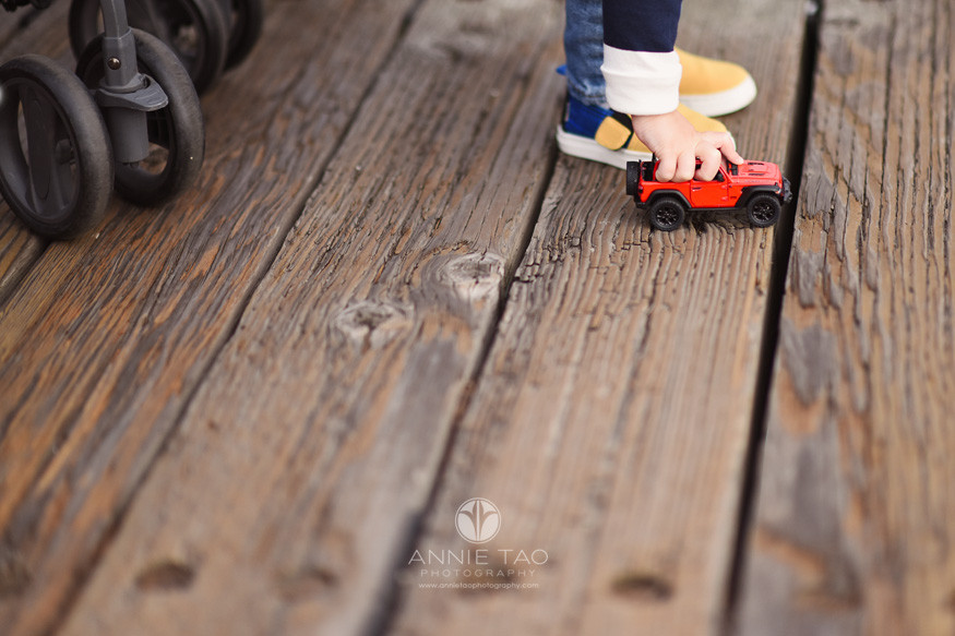 San-Francisco-lifestyle-children-photography-toddler-hand-plays-with-red-toy-car-from-stroller